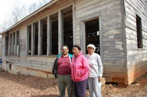 Phillip Ervin, left, Charity Ray, center, and Dorothy Coone stand in front of the school they once attended and now hope to help restore.