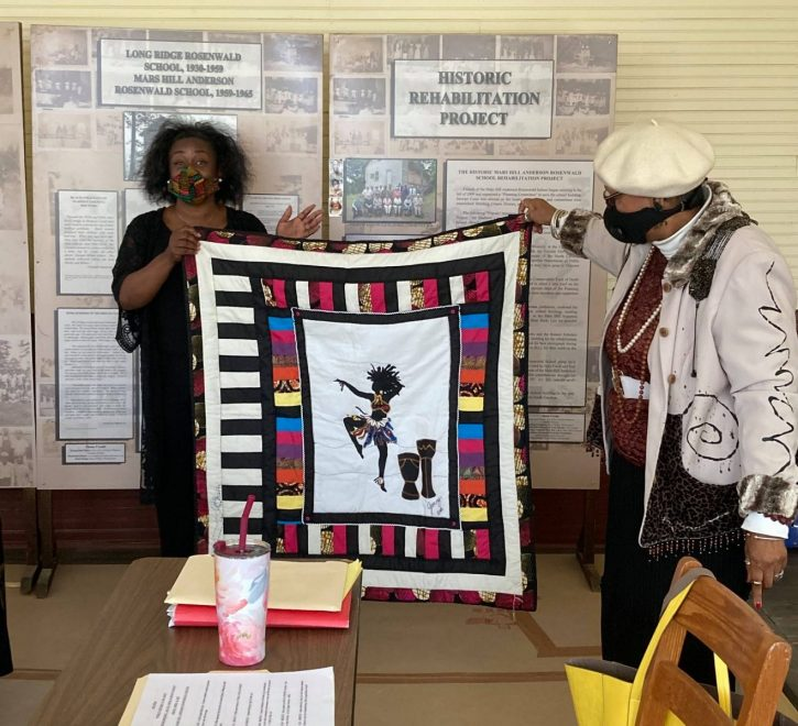 Jenny Pickens (left) and Fatimah' Shabazz hold an example of a quilt Pickens made.